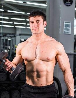 Парень мускулистого культуриста, стоящего на тренажерном зале и позирующего трехглавую мышцу
