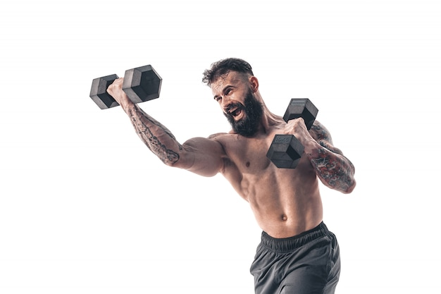 Muscular bodybuilder holding dumbbells on white background