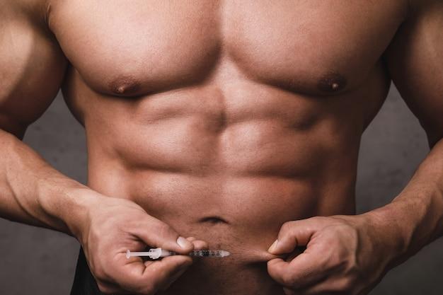 筋肉のボディービルダーは腹に皮下注射をする準備ができています