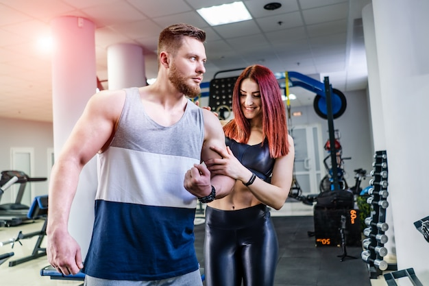 Muscular bodybuilder is showing his biceps to the pretty young woman in sports center. amazed female touching male's arm while standing close to the athlete in crossfit gym.