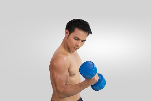 Muscular bodybuilder lifting and pumping up with dumbbell on isolated background