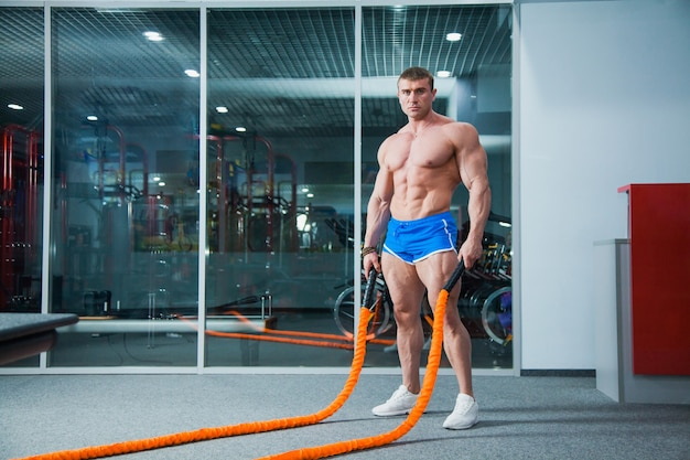Muscular bodybuilder with battle rope at modern gym. battle rope exercise in crossfit workout.