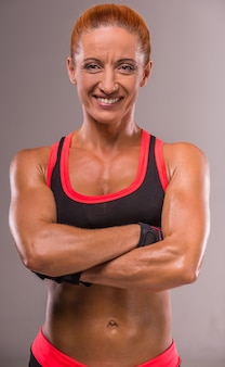 Muscular bodybuilder woman is looking at the camera.
