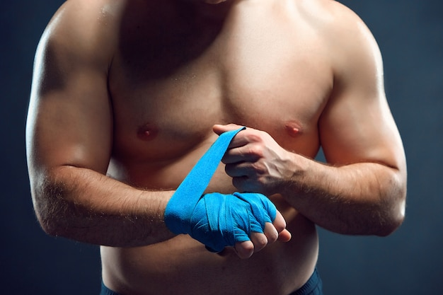 Muscular boxer bandaging his hands on gray