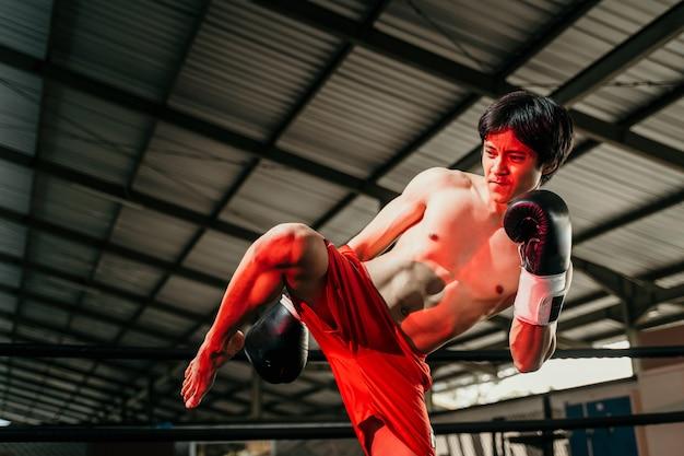 권투 글러브를 입은 근육질 복서 전투기가 붉은 조명으로 어두운 링에서 무릎을 걷어차 게합니다.