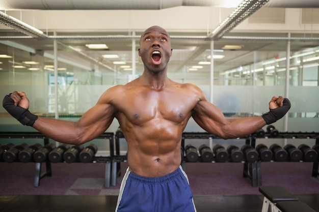 Muscular boxer shouting in health club