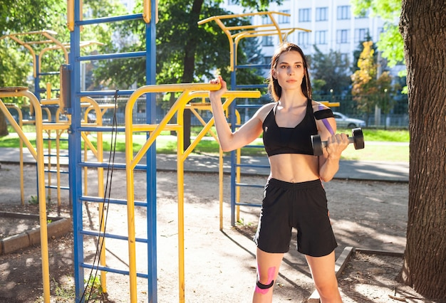 Muscular brunette pretty woman training arm using dumbbell in park