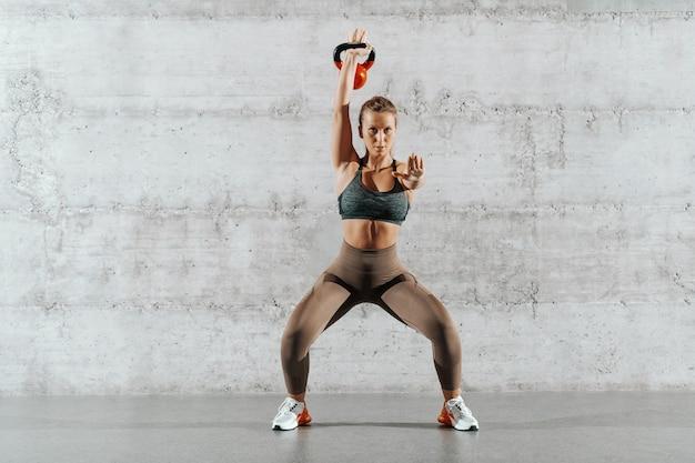 ポニーテールの筋肉ブルネットと灰色の壁の前で手でケトルベルでスクワット持久力を行うスポーツウェア。
