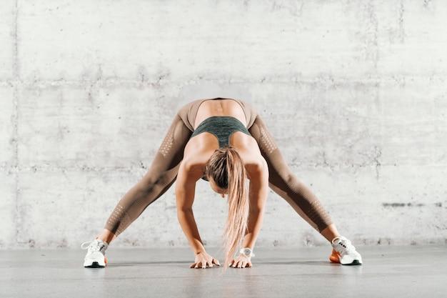 ポニーテールの筋肉ブルネットと足でストレッチ運動を行うスポーツウェアでレンガの壁の前に広がります。