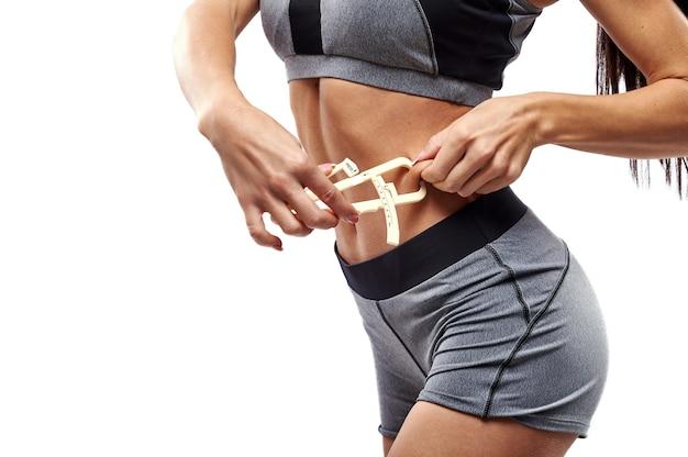Muscular build fit woman measuring her body fat on abdomen using caliper. closeup
