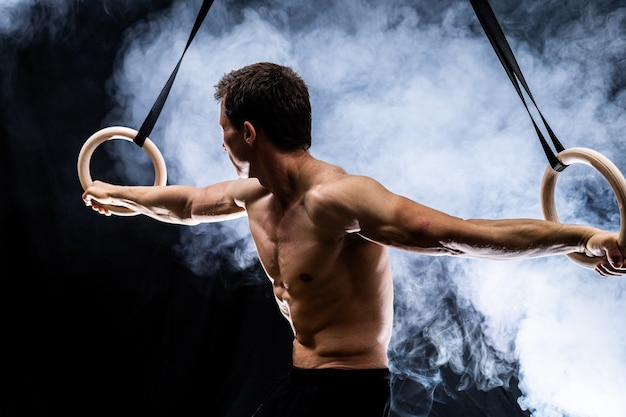 Muscular build man doing calisthenics on gymnastics rings indoor on black, smoked background