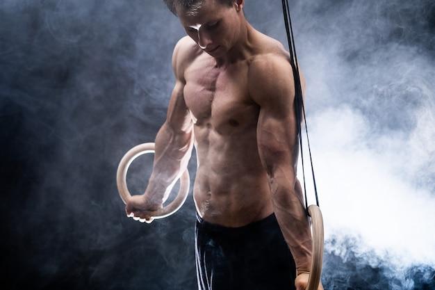 Мускулистый мужчина делает художественную гимнастику на гимнастических кольцах в помещении на черном копченом фоне, концепция мотивации желания и страсти