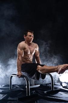 평행선 막대에서 체조를 하는 근육질의 남자. 동기 부여, 욕망 및 열정의 개념입니다.