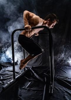 Мускулистый мужчина делает художественную гимнастику на параллельном баре в помещении на черном фоне, концепция здорового образа жизни и власти