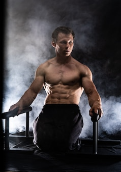 검은 훈제 배경의 실내 평행 바에서 체조를 하는 근육질의 남자