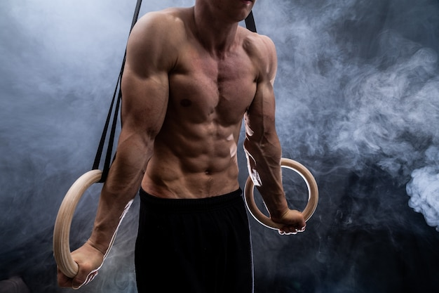 Muscular build man doing crossfit on gymnastics rings indoor on black, smoked background
