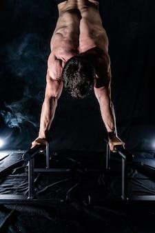 Мускулистый мужчина делает кроссфит на баре parallels в помещении на черном фоне, концепция здорового образа жизни и художественной гимнастики