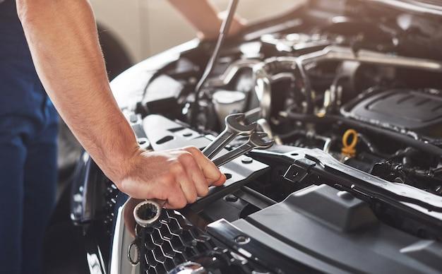 Мускулистый работник автосервиса ремонтирует автомобиль.
