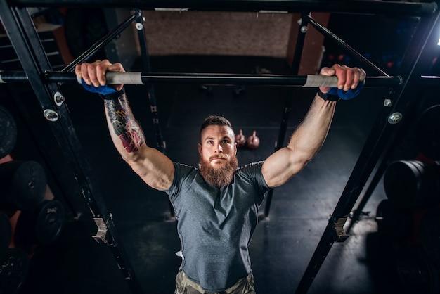 筋肉の白人のひげを生やした男は、プルアップを行い、彼の上腕二頭筋をトレーニングし、クロスフィットジムに戻ります。