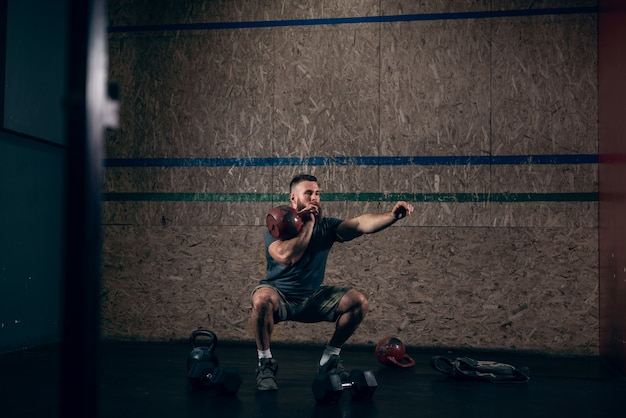 Muscular caucasian bearded man lifting kettlebells in gym.