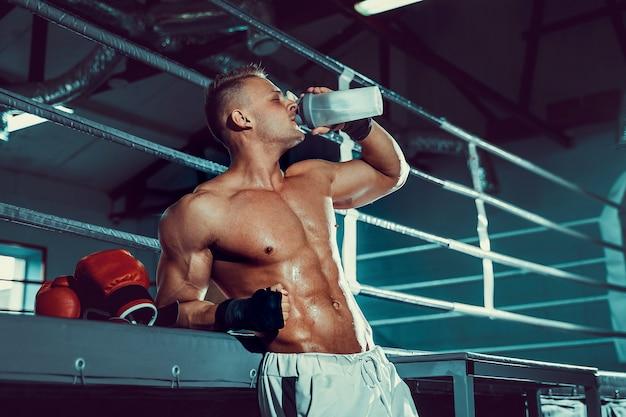권투 운동 후 휴식 다이어트 근육 백인 남자와 체육관에서 셰이 커에서 마시는 물.
