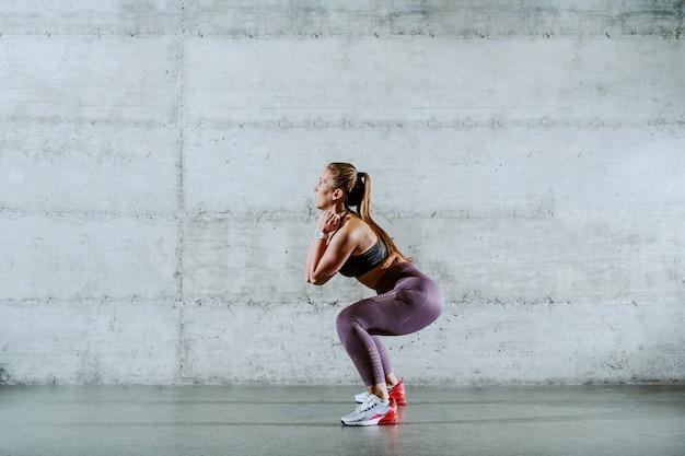 Muscular caucasian sportswoman in sportswear doing squats endurance indoors.