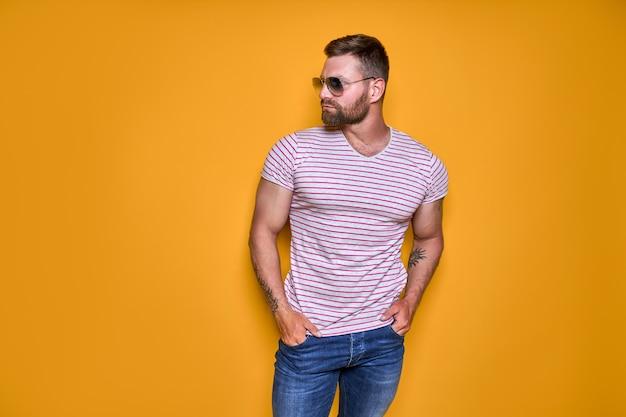 셔츠 청바지와 노란색 스튜디오에 서 있는 세련된 선글라스를 입은 근육질의 자신감 있는 수염 남성