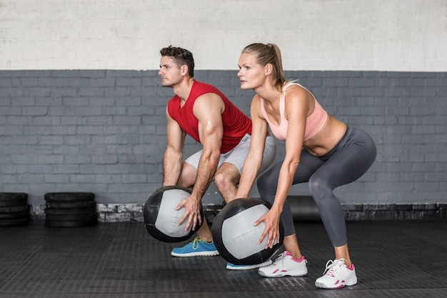 Muscular couple doing ball exercise
