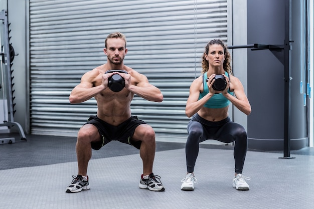 Kettlebellsで運動する筋肉質のカップル