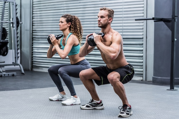 Muscular couple exercising with kettlebells