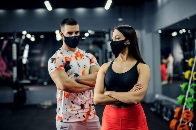 무기와 체육관에 서있는 근육질의 부부는 코로나 바이러스 동안 얼굴 마스크와 교차했습니다.