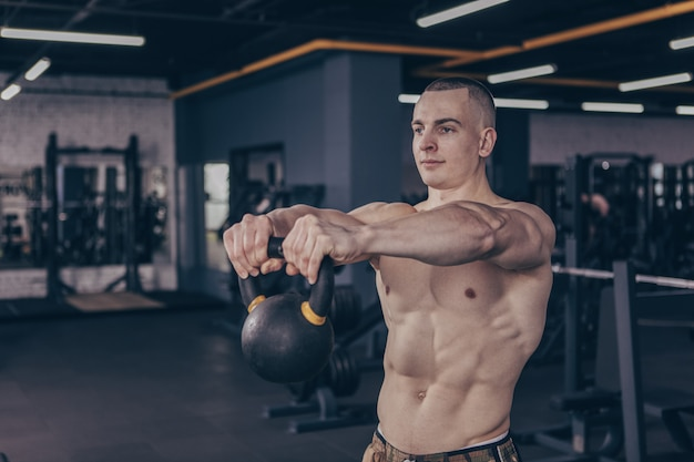 Muscular crossfit athlete working out with kettlebell