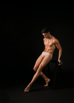 Muscular dancer leaning on barre