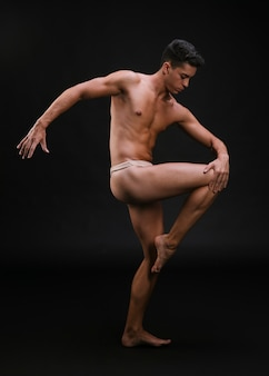 Muscular dancer stretching leg