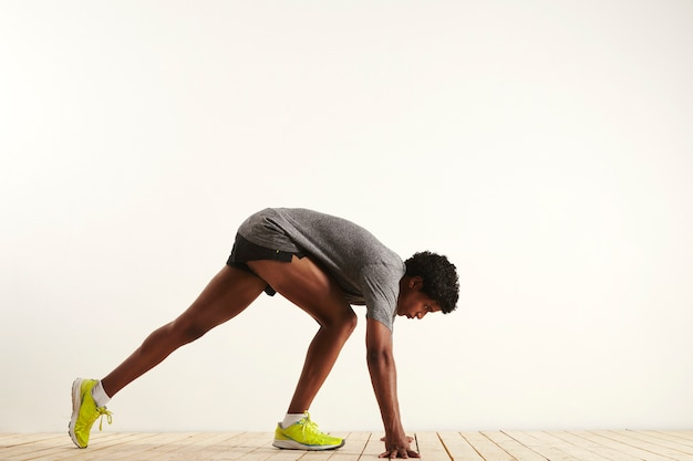 Muscular dark skinned sprinter in gray shirt, black shorts and neon yellow sneakers getting into starting position shot from the side against white wall