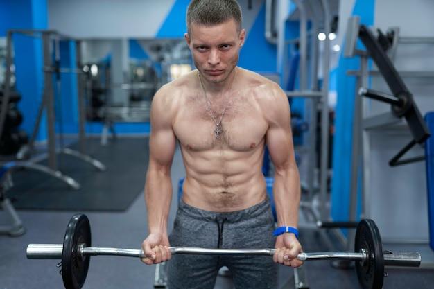 알몸의 몸통을 가진 근육질의 남자는 바벨을 팔뚝으로 들어 올리는 데 운동을합니다.