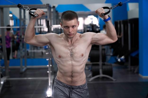벌거 벗은 몸통을 가진 근육질의 친구는 크로스 오버에서 이중 팔뚝을하고 체육관에서 운동합니다.