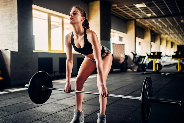 スポーツジムでバーベルを使ってトレーニングする筋肉質の女性アスリート。フィットネスクラブで体重を伴う女性の運動