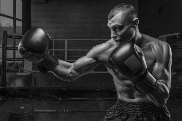 Muscular fighter boxing against the ring. mixed martial arts concept.