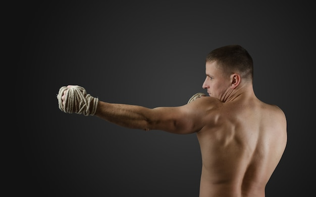 手に麻縄を使って暗い表面で筋肉の戦闘機ムエタイトレーニング