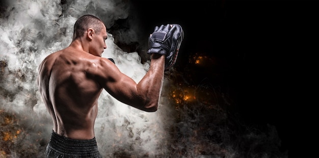 Muscular fighter posing with boxing paws against smoke and fire. mixed martial arts concept.
