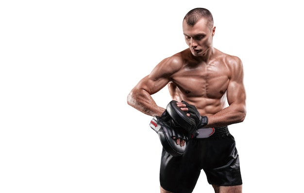Muscular fighter posing with boxing paws. mixed martial arts concept.