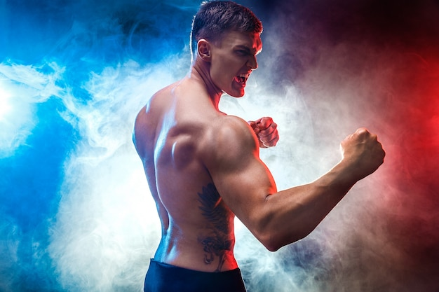 Muscular  fighter punching in smoke. colour background.