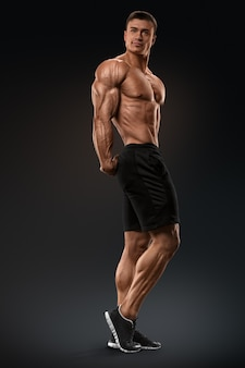 Muscular and fit bodybuilder fitness male model posing over black background strong and handsome you