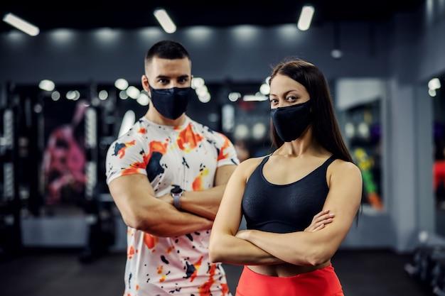 팔을 교차 체육관에 서 얼굴 마스크와 근육 맞는 커플. 건강한 습관, 코로나 바이러스 예방, 보디 빌딩