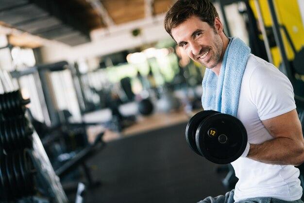 上腕二頭筋でダンベルを使ってエクササイズをしているジムで運動している筋肉のフィットの男