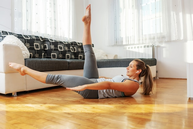 Muscular fit sportswoman lying on the floor at home and doing fitness exercises for her abs