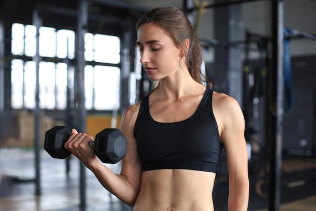 ジムで骨格筋を鍛える筋肉にフィットする女性。