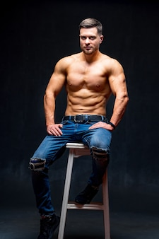 Muscular and fit young bodybuilder fitness male model posing on chair. studio photo. full size portrait.