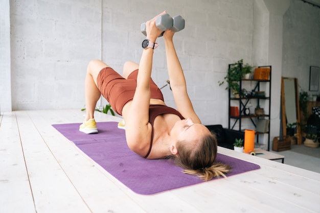 窓枠のエクササイズマットの上に横たわっているダンベルで運動するスポーツウェアを身に着けている完璧な運動体を持つ筋肉にフィットする若い女性。健康的なライフスタイルと家庭での身体活動の概念。